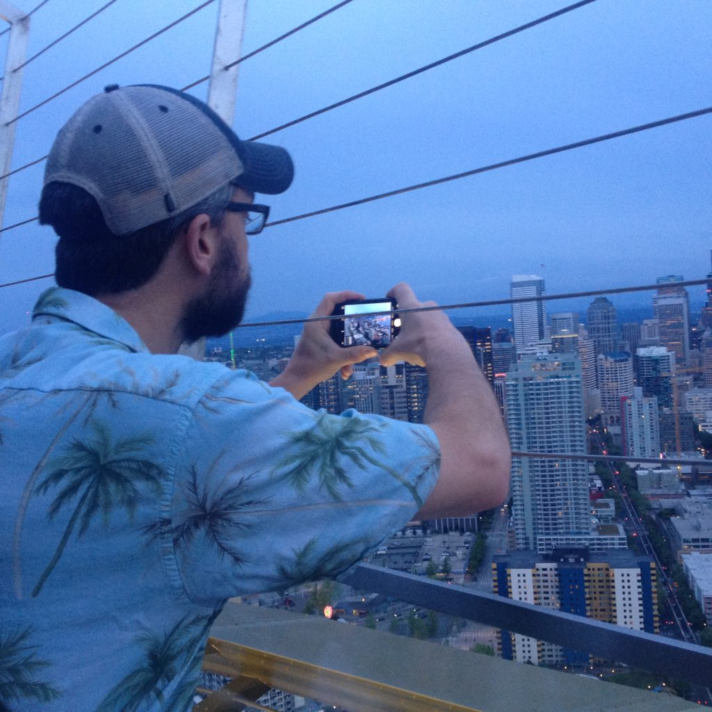 Rob on top of the Space Needle taking a picture of the Seatle Skyline
